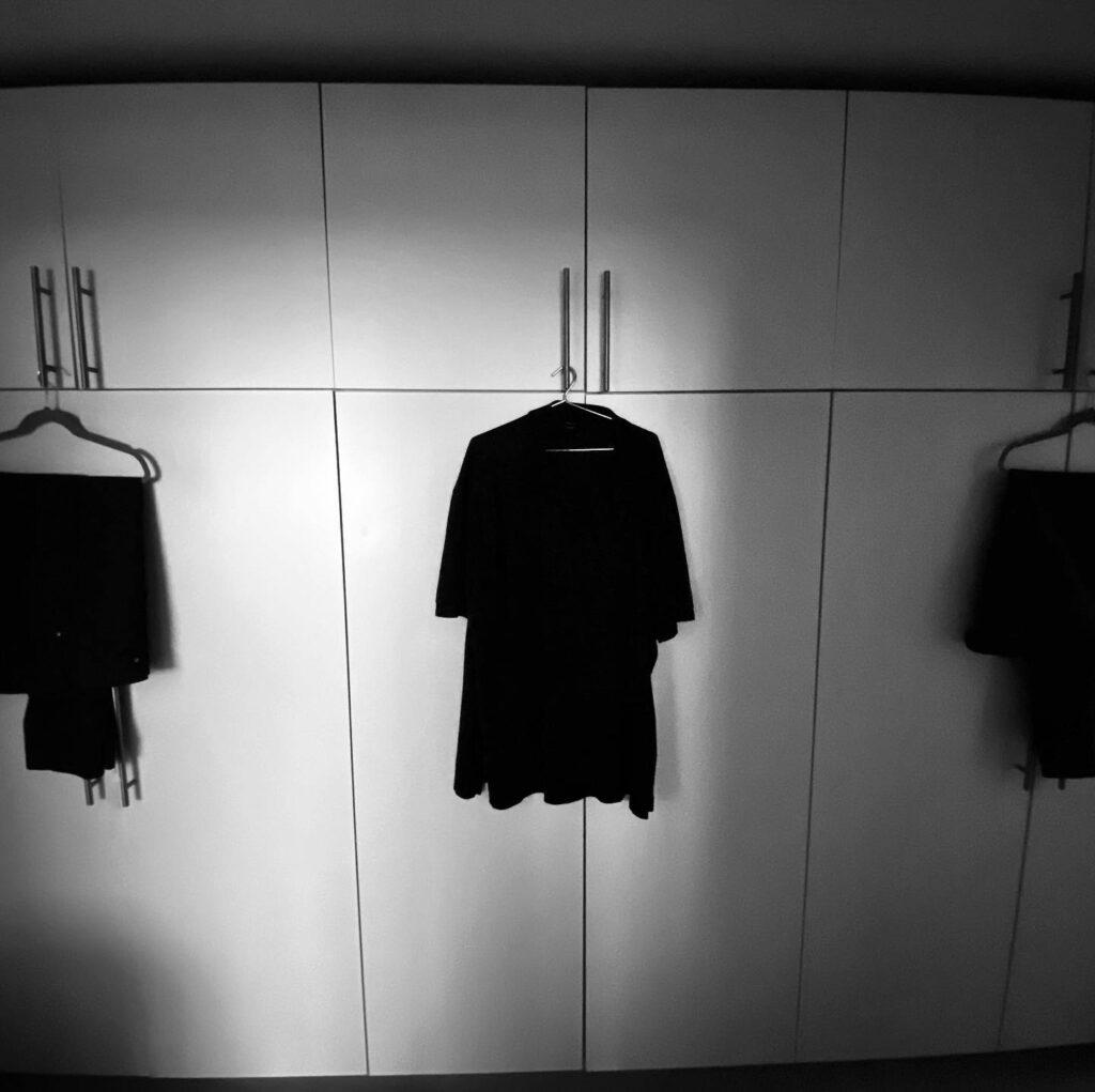 Eine Hose und zwei Shirts hängen nebeneinander auf einem Kasten