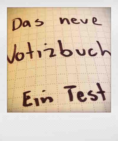 """Fotos eines Notizbuchausschnitts, Schriftzug """"Das neue Notizbuch - Ein Test"""""""