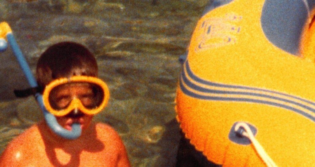 Kind (Robert Lender) mit Tauchermaske und Schnorchel. Halb im Wasser stehend. Daneben Teil eines Schlauchboots im Bild