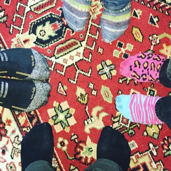 4 Paar Füsse in bunten Socken im Kreis stehend auf bunten Teppich