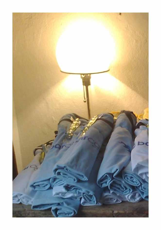 Lampe, davor liegen auf einem Tisch übereinander gestapelt und zusammengerollte T-Shirts