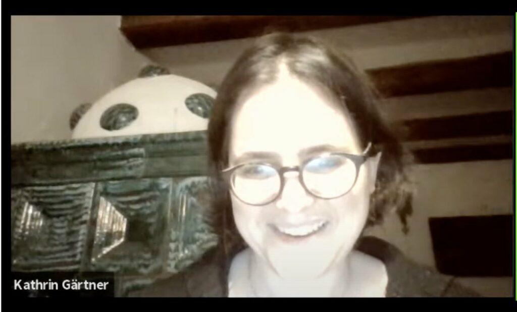 Kathrin Gärtner Profil in die Kamera schauend, dahinter ein Kachelofen