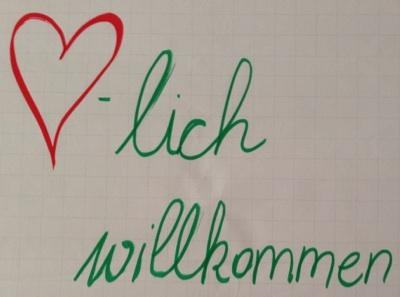 """Plakat mit der Aufschrift """"Herzlich willkommen"""" Herz ist als Bild eines Herzen dargestellt"""