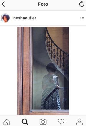 Ines Häufler fotografiert ihr Spiegelbild in einer Glastüre - im Hintergrund geschwungene Treppe
