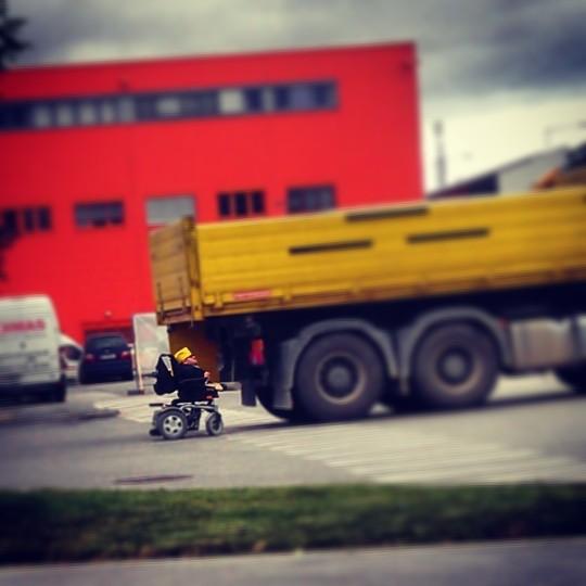 LKW, dahinter ein Mann im Rollstuhl mit gelber Mütze (Martin Habacher, @mabacher)