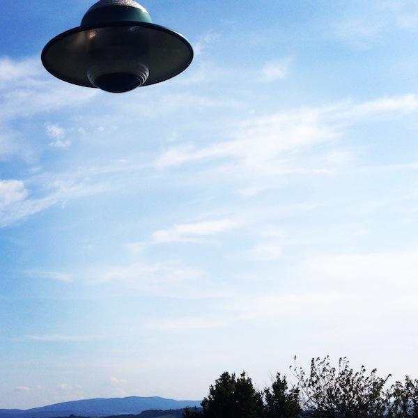 Fliegende Untertasse fliegt am Himmel über ein paar Bäume