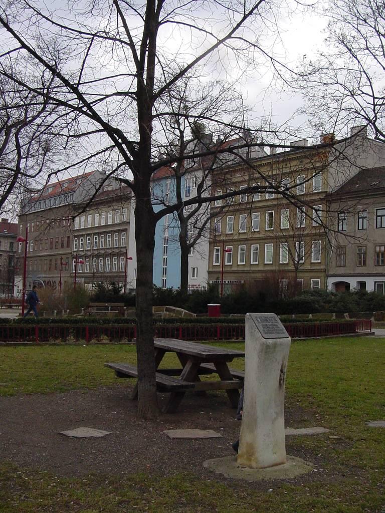 Lindenbaum, daneben Parkbank und davor ein Stein mit Inschrift