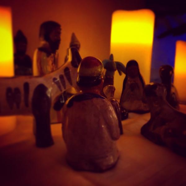 bemalte Krippenfiguren aus Ton von leuchtenden Kerzen umgeben