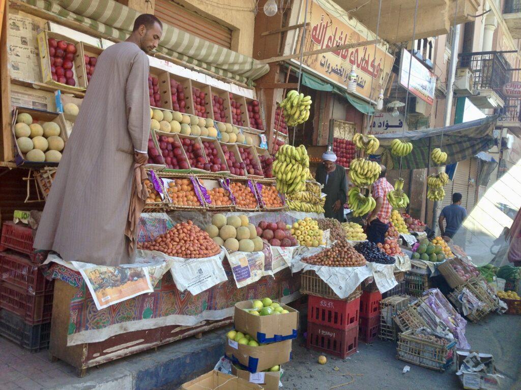 Marktstand mit vielfältigen Früchten, Mann steht auf einem Kasten
