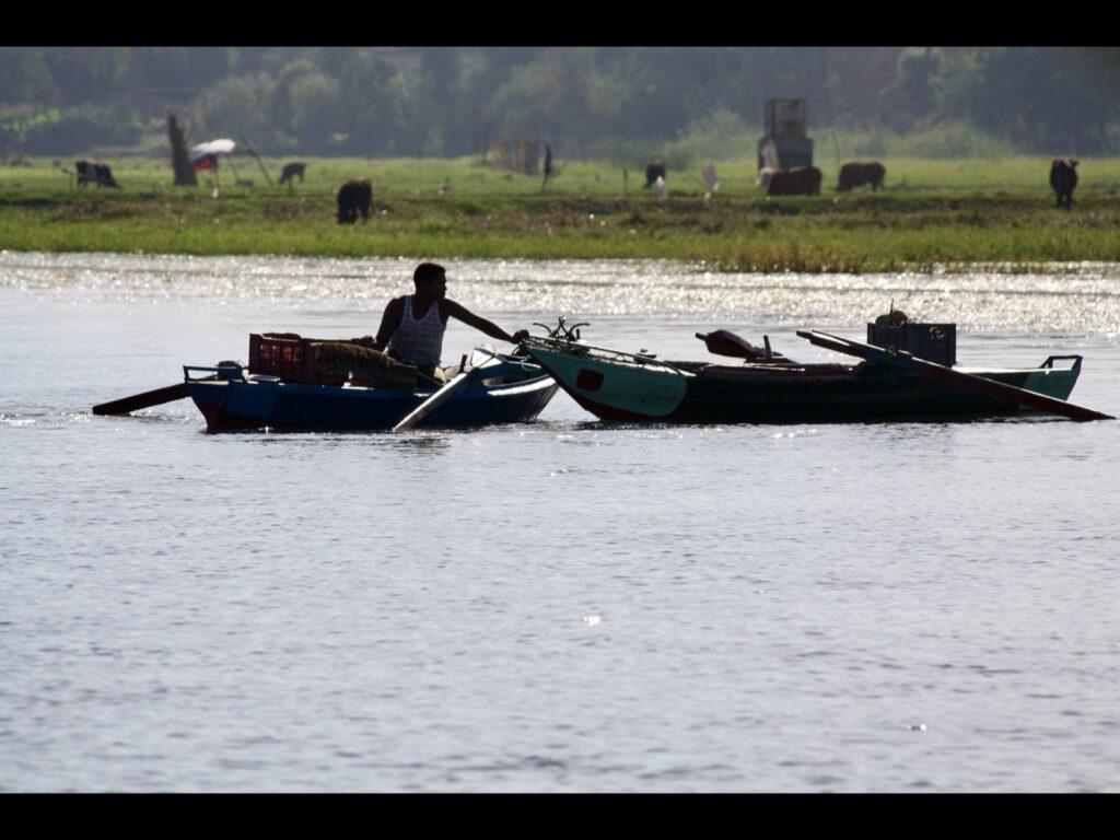 Mann in einem kleinen Boot am Wasser zieht ein zweites Boot zu sich