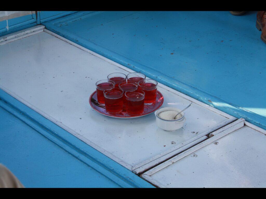 Mehrere Gläser mit roter Flüssigkeit und eine Schale mit Zucker