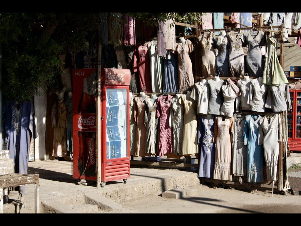 Colaautomat mit Kartons darinnen, daneben Stangen mit Frauenkleidern